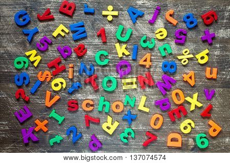 Background from colorful magnetic letters and numbers over a wooden background