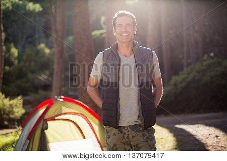 Man smiling and posing on a camp site
