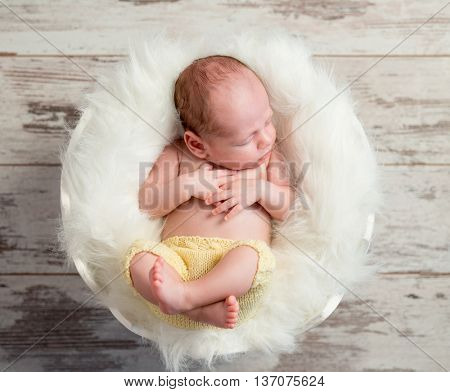 funny sleepy baby in round white cot with legs up, top view