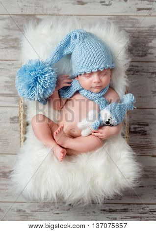 lovely sleeping baby in blue hat with big pompon on fluffy cot, top view