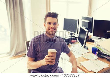 business, startup and people concept - happy businessman or creative male office worker with computers drinking coffee