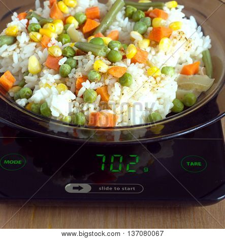 Translucent white plate with rice and vegetables is at home kitchen electronics scales to count calories in food on wooden table. Front view closeup
