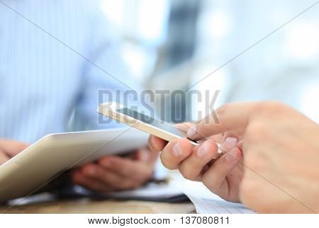 Smartphone handheld in closeup colleagues working in background