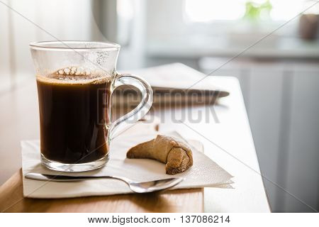 Glass of black coffee arranged with spoon and croissant on wooden table closeup