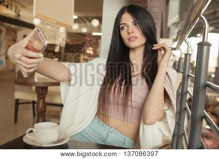 beautiful young woman sitting alone in cafe and make selfie. Focus on woman.Blurred background.