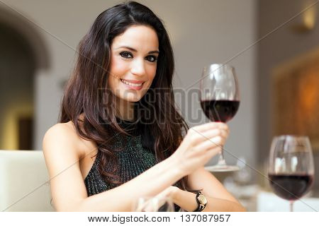 Charming woman holding a lass of red wine poster