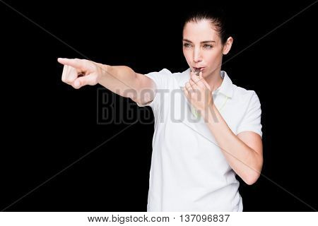 Female athlete blowing a whistle and pointing on black background