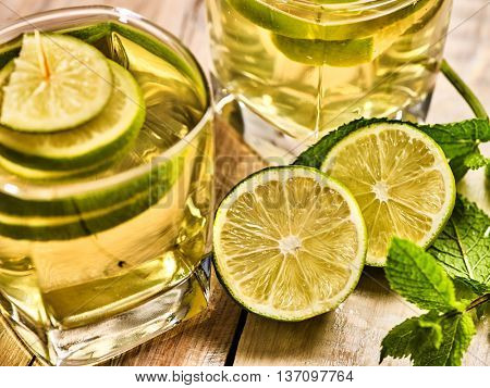 Alcohol drink. On wooden boards two glasses with alcohol green transparent drink. A drink number eighteen mojito cocktail with half lime and mint . Top view. Country life. Light background.