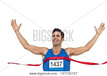 Cheerful winner athlete crossing finish line with arms raised on white background
