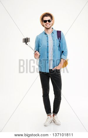 Full length of smiling young man with backpack and mobile phone on selfie stick over white background