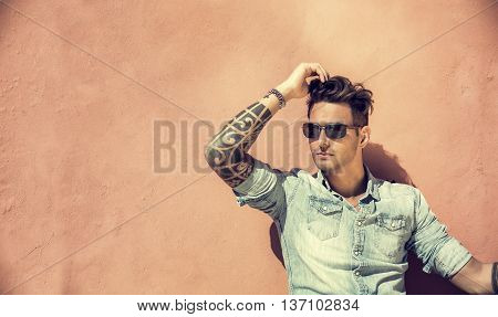 Portrait of handsome man with tattoo on arms sitting and leaning on orange wall in the sun, wearing sunglasses, looking away to a side