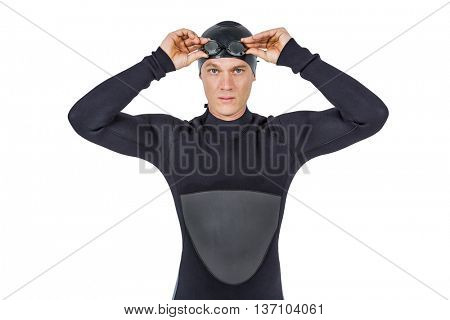 Portrait of swimmer in wetsuit wearing swimming goggles on white background