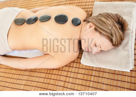 Resting caucasian woman lying on a massage table with hot stones in a health spa
