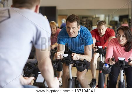 Instructor in foreground with spinning class at a gym