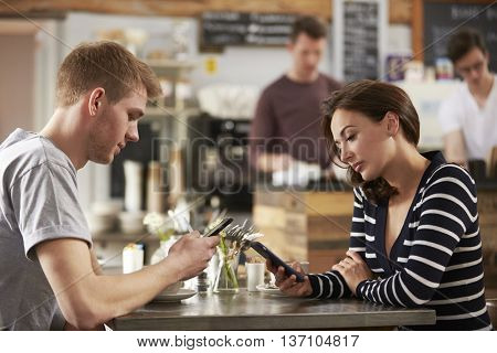 Adult couple sitting in a cafe using smartphones, close up