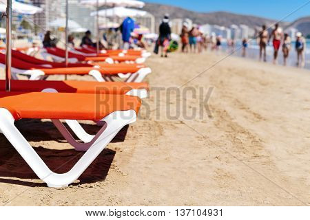 closeup of some sunloungers and umbrellas in San Antonio Beach in Cullera, Spain, with the Mediterranean sea and some unrecognizable sunbathers and walkers in the background