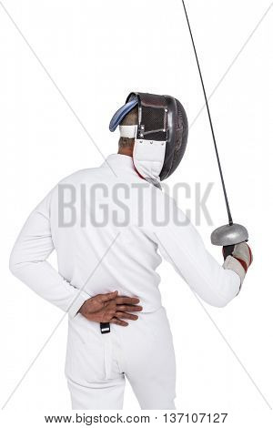 Rear view of man wearing fencing suit practicing with sword on white background
