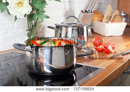 pan on the stove with vegetables in kitchen interior home