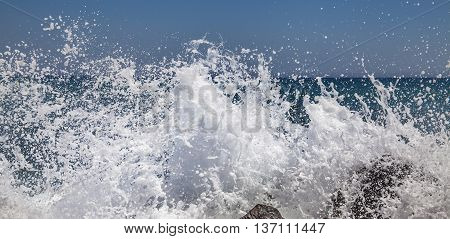 Sea splashes in a sunny weather hit against stones