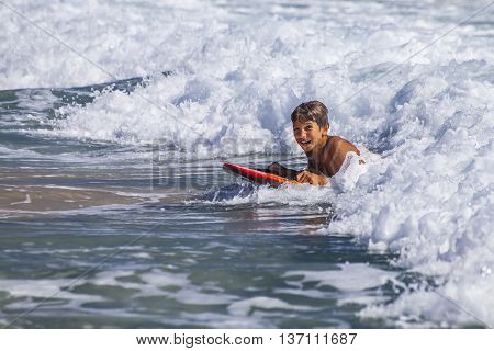 The boy swims on a board in waves