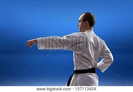 Adult master is beating punch arm on a blue background