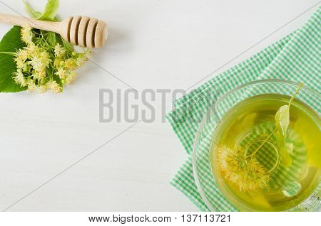 Cup of herbal tea with fresh branch linden blossom on a white wooden background. Folk, alternative, complementary medicine, traditional medicine.