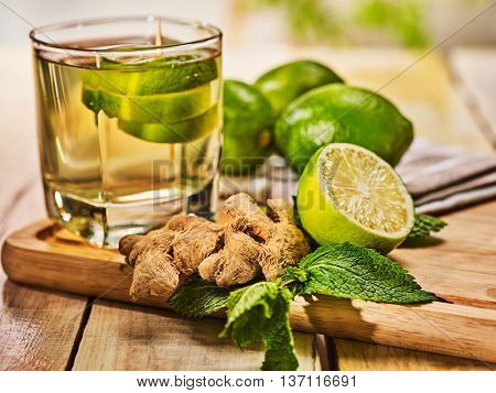 Healthy detox drink with ginger . On wooden boards glass with green tea and mint. A mint ginger drink number twenty four with half lime and napkin. Country life. Light background.