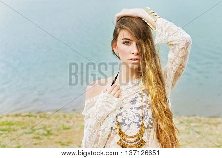 Portrait of gorgeous young woman with long blonde hair at the beach, posing, wearing sheer beige dress, bikini and golden necklace and bracelet. Retouched, natural light.