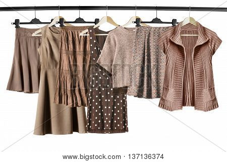 Brown and beige clothes on clothes racks isolated over white