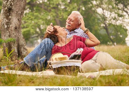 Senior couple old man and woman in park on weekend activity. Grandpa and grandma doing picnic in wood. Concept of retirement age and love.