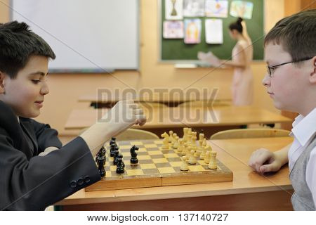 two students during break between lessons in classroom playing chess, girl in background at blackboard, shallow dof