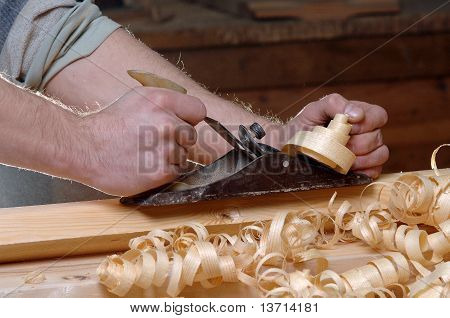 Man hands with carpenter's plane on wooden background