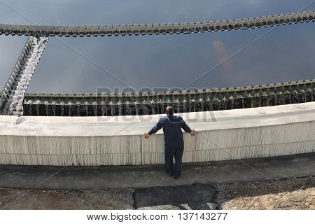 Biological wastewater treatment is carried out in aeration tanks of propellant, worker stands near primary settler
