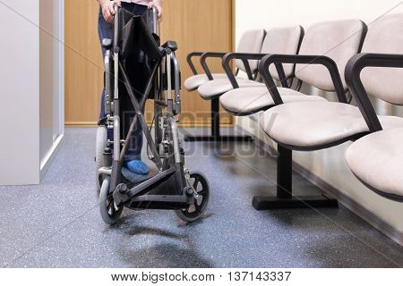 woman folds or unfolds black wheelchair in lobby of hospital