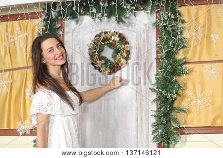 lovely woman with elegant style standing near door of house sham, knocking at the door, look at us.