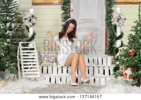 Full portrait of young woman sitting on threshold of fake home and listening music in headphone and dance sitting, head down, smile. Christmas interior studio