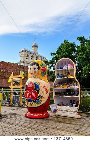 VELIKY NOVGOROD RUSSIA -JUNE 11 2016. Belfry of St Sophia cathedral with big colorful Russian doll matrioshka on the foreground and souvenir trade in Veliky Novgorod Russia