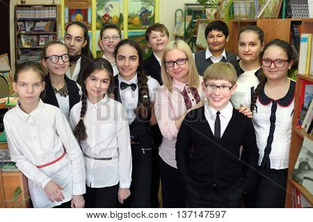 Eleven students in school library stand in rows one after other with teacher, they all look at camera and smiling