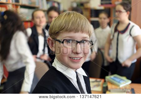 student in black jacket and glasses on background of shelves with books and other students, smiling at camera, shallow dof
