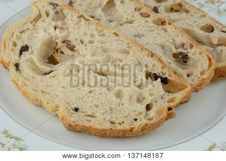 Close up of three slices of Kalamata olive bread on white plate