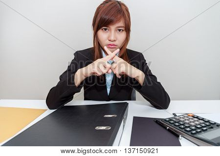 Businesswoman says no with cross fingers on at her office.