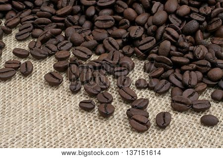 black coffee beans on a beige fabric