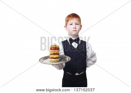 Little waiter stands with tray serving big double hamburger. Redhead Child boy in suit plays restaurant servant, gives burger isolated at white background