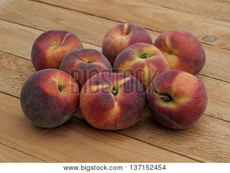 red tasty peaches stacked on pine boards