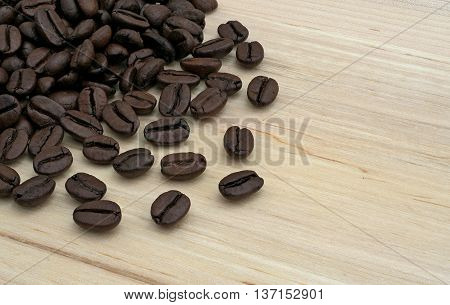 black coffee beans on bright wooden board