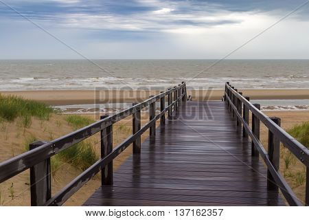 Wooden staircase leading into stormy sky and sea at De Haan Belgium