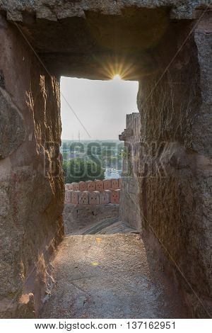 Chettinad India - October 16 2013: View out of Thirumayam Fort through one battlements opening upon village with sun dispersing rays captured on wall.