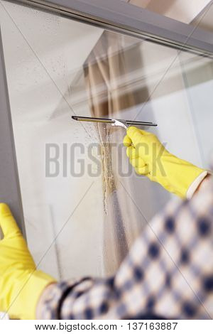 Mature man cleaning windows using squeegee
