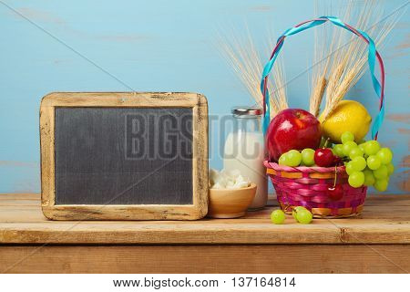 Jewish holiday Shavuot celebration with milk and fruits basket on wooden table.