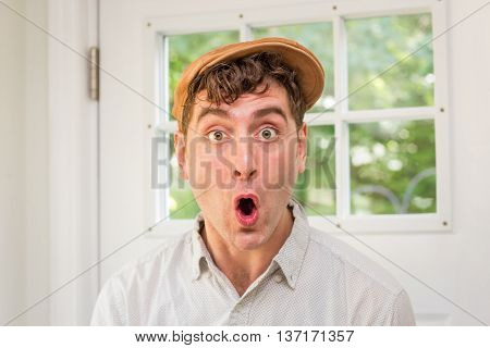 Young handsome curly haired man wearing newsboy hat gasping from excitement